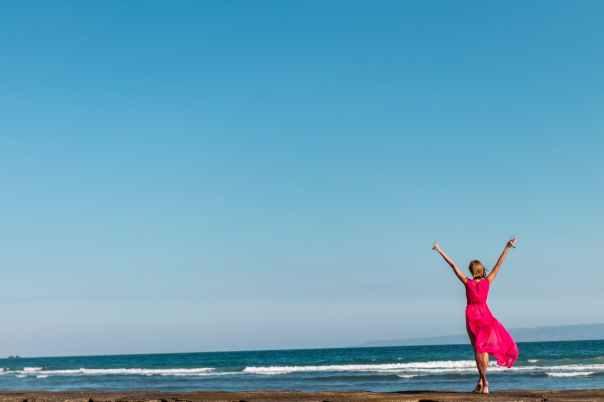 woman wearing pink dress standing on shore